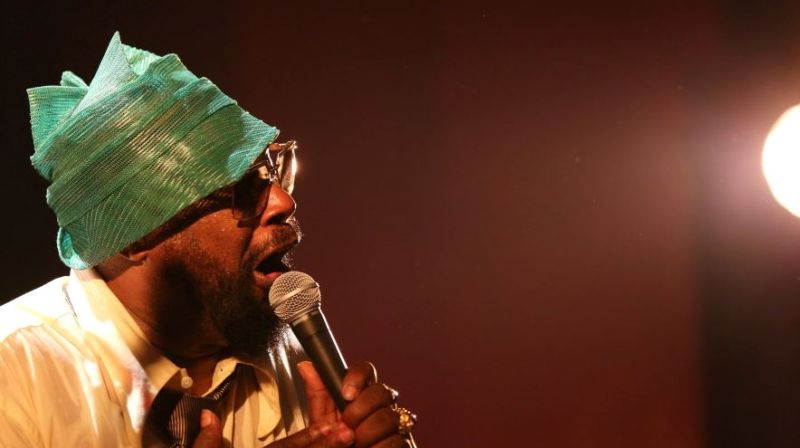 George Clinton singing in a green hat